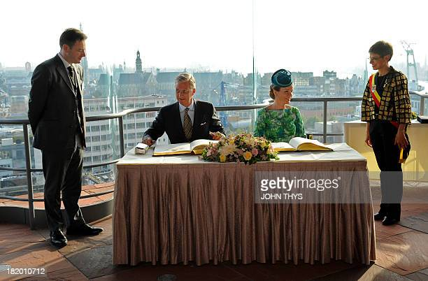 Queen Mathilde and King Philippe of Belgium sign a register as Antwerp's mayor Bart De Wever and Antwerp's province governor Cathy Berx look on...