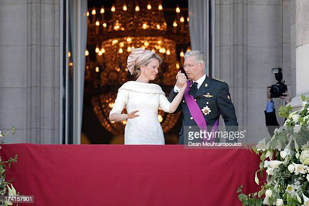 Queen Mathilde of Belgium and King Philippe of Belgium are seen greeting the audience from the balcony of the Royal Palace during the Abdication Of...