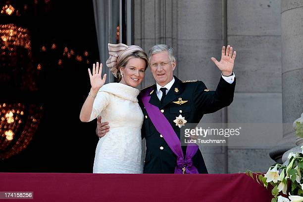 Queen Mathilde of Belgium and King Philippe of Belgium wave to the audience from the balcony of the Royal Palace during the Abdication Of King Albert...