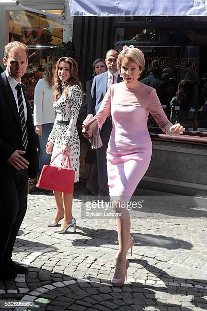 Queen Mathilde of Belgium and Queen Rania of Jordan pose for photographers after a visit to a chocolate shop during a royal guided tour through the...