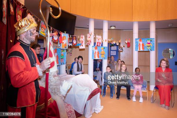 Queen Mathilde of Belgium is welcomed by at Santa Claus and Black Pete during a visit to the Queen Paola Hospital for Children on December 06 2019 in...