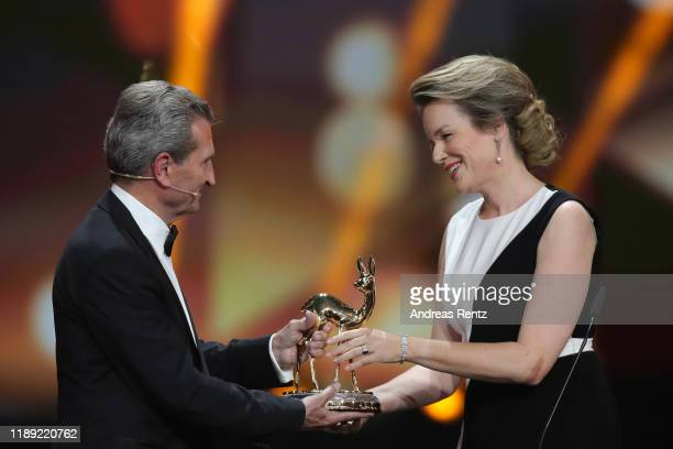 Queen Mathilde of Belgium receives an award from Guenter Oettinger on stage during the 71st Bambi Awards show at Festspielhaus BadenBaden on November...
