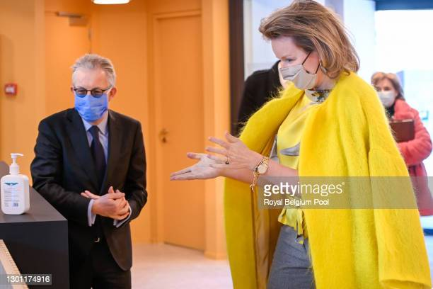 Queen Mathilde of Belgium sanitizes her hands prior to meet with representatives of the fashion and clothing sector in a round table organized by...