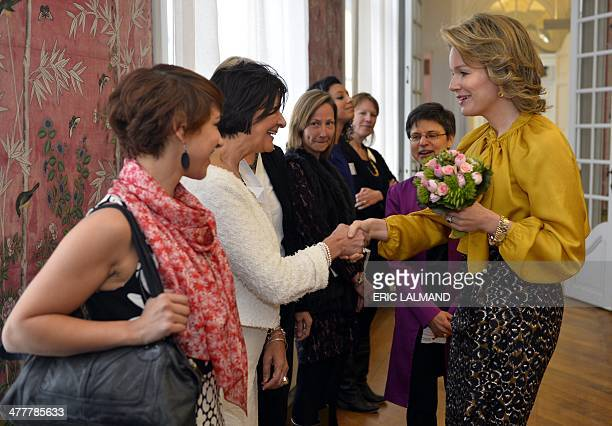 Queen Mathilde of Belgium shakes hands with one of the leading women from various sectors in the Antwerp province, on March 11 in Hingene. AFP PHOTO...