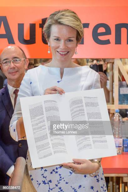 Queen Mathilde of Belgium shows the declaration of the human rights that was printed with an old print press at the pavilion of the French guest of...