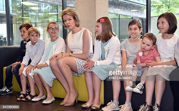 Queen Mathilde of Belgium sits with children during a visit to the Centre for Human Genetics of the Catholic University of Leuven on June 22 in...