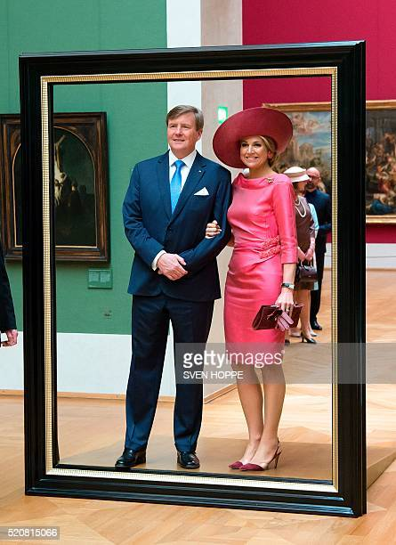 Queen Maxima and King WillemAlexander of the Netherlands pose in a giant picture frame as they tour through the HollaenderSaal of the Alte Pinakothek...
