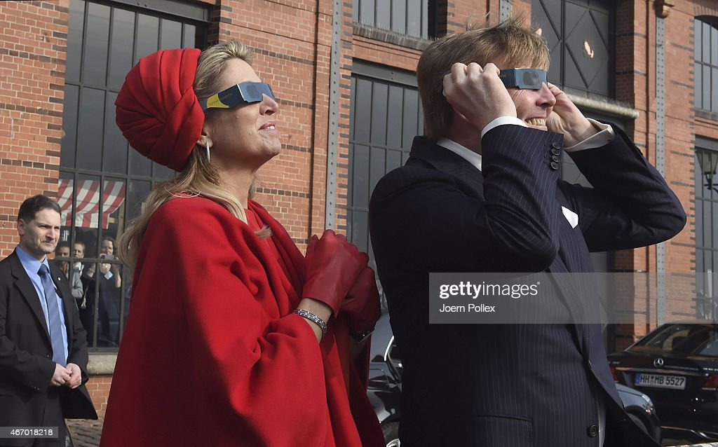 Queen Maxima and King Willem-Alexander of the Netherlands wear sunglasses as they watch a partial solar eclipse at the Fischautkionshalle during their state visit on March 20, 2015 in Hamburg, Germany.