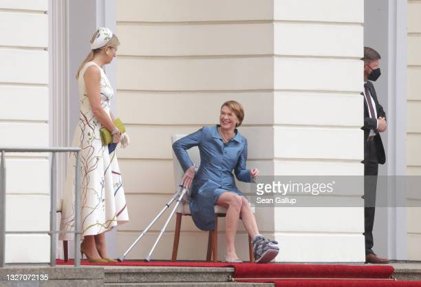 Queen Maxima of the Netherlands and German First Lady Elke Budenbender sit sheltered from the rain as their husbands review a guard of honour at...