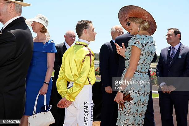 Queen Maxima of the Netherlands chat with jockey Steven Parnham in the mounting yard during a visit to Ascot Racecourse on Melbourne Cup Day on...