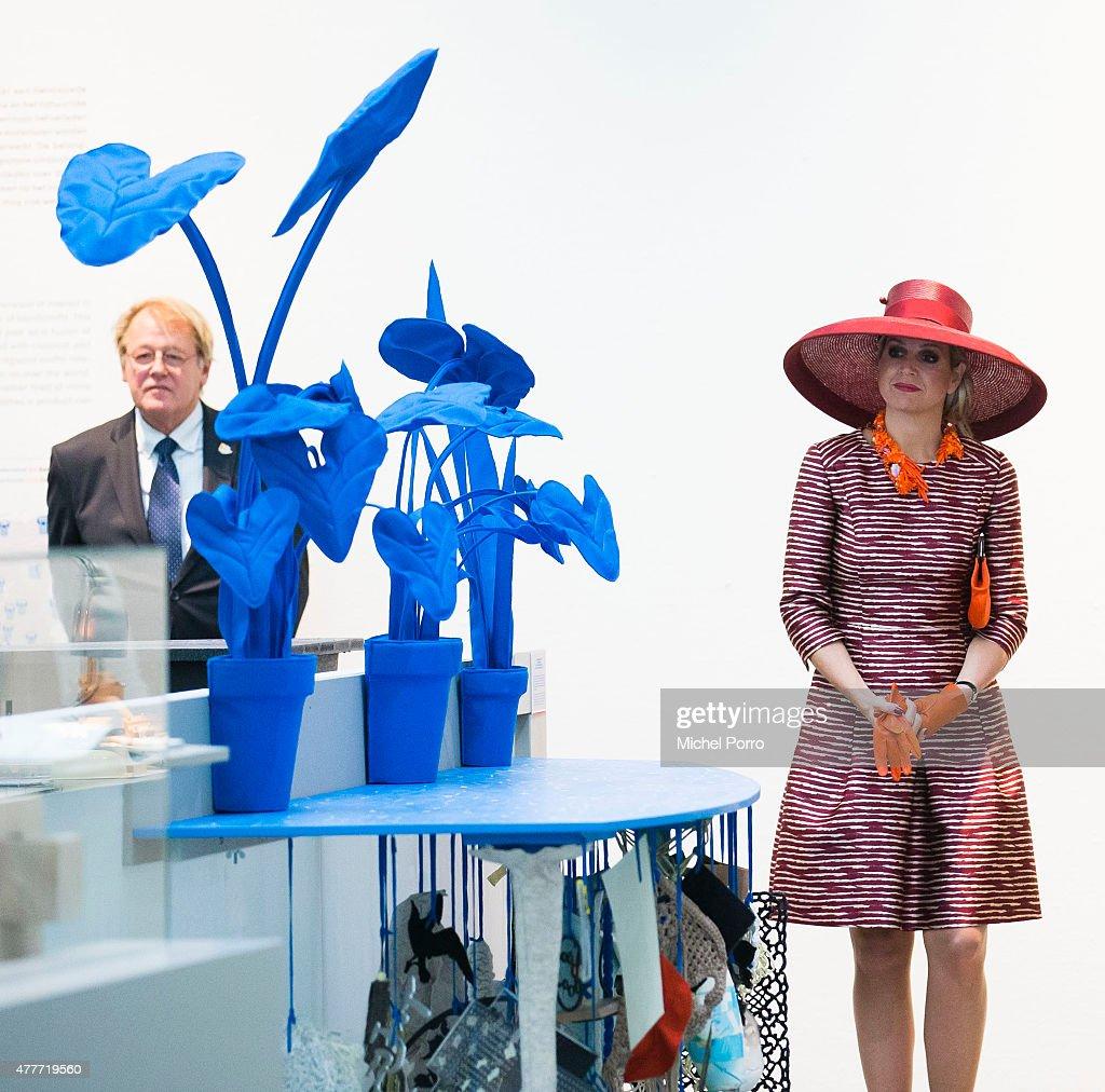 Queen Maxima of The Netherlands looks at felt plants designed by Wandschappen Ivo van den Baar and Nicole Driessens during the opening of the Design Derby Netherlands - Belgium on June 19, 2015 in Rotterdam Netherlands.