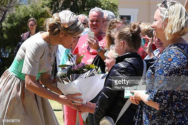 Queen Maxima of the Netherlands receives a boquet of flowers from a young girl on arrival at the Shipwreck Galleries on October 31, 2016 in...