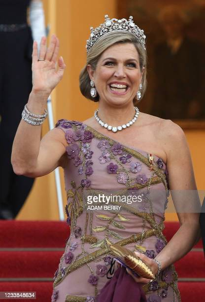 Queen Maxima of the Netherlands waves as the royal couple arrive for a state dinner in their honour at the Bellevue presidential palace in Berlin on...