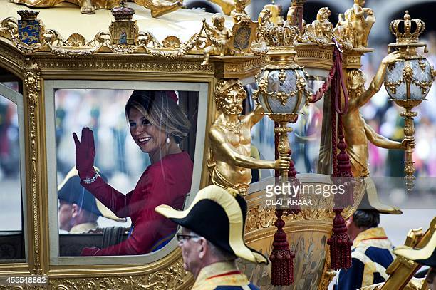 Queen Maxima waves as she sits in a carriage on September 16 2014 in The Hague during Prinsjesdag the openingday of Dutch parliament taking place...