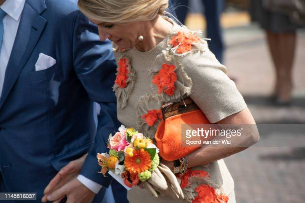 Queen Maxima wearing a sand colored culotte and top designed by Natan and purse by the Belgian brand A Bag with a Story and a hat designed by...