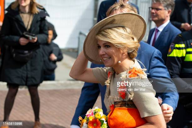 Queen Maxima wearing a sand colored u2019culotte and top designed by Natan and purse by the Belgian brand A Bag with a Story and a hat designed by...