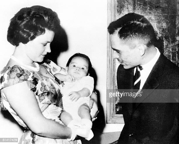 Queen Muna elHussein born Antoinette Gardiner holds her son Prince Abdullah as Hussein Ibn Talal King of Jordan looks on 31 May 1962 in Amman Queen...