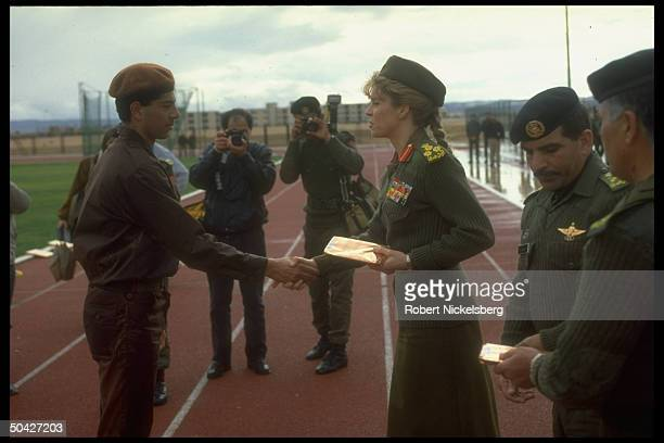 Queen Noor, jaunty in her mil. Uniform, shaking soldier's hand, w. Officers & photographers, at People's Army reserve unit graduation .