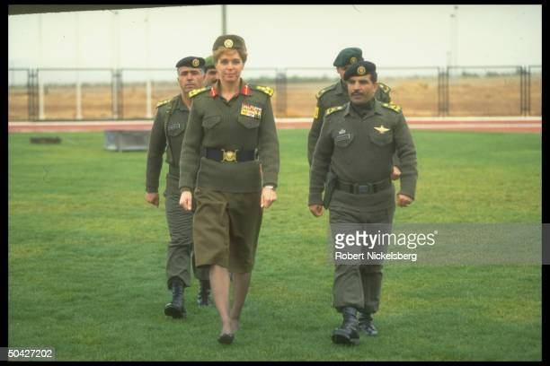 Queen Noor jaunty in her mil uniform striding smartly w retinue of officers during People's Army reserve unit graduation