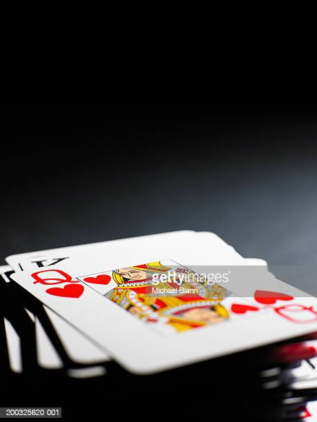 Queen of hearts on pile of playing cards, close-up