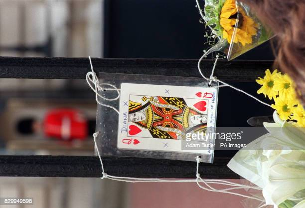 A Queen of Hearts playing card joins the floral tributes to Diana Princess of Wales outside Buckingham Palace