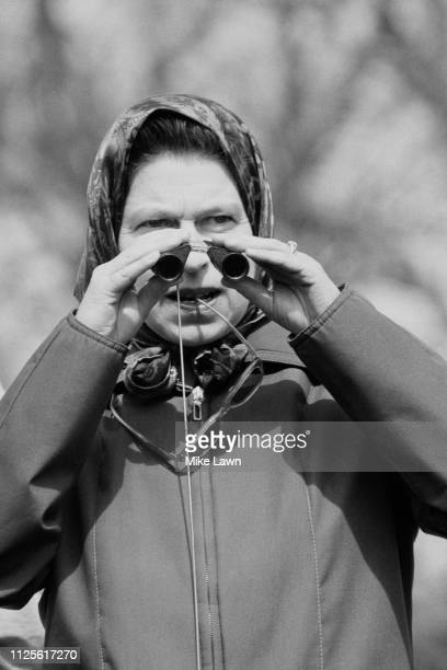 Queen of the United Kingdom Elizabeth II with binoculars while watching the cross-country section at Badminton Horse Trials, UK, 21st April 1980.