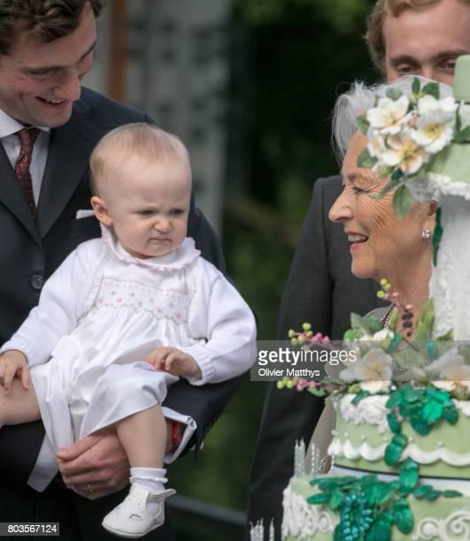 Queen Paola of Belgium looks at Prince Amedeo of Belgium, Archduke of Austria-Este and his baby daughter Anna-Astrid van Oostenrijk-Este in front of...