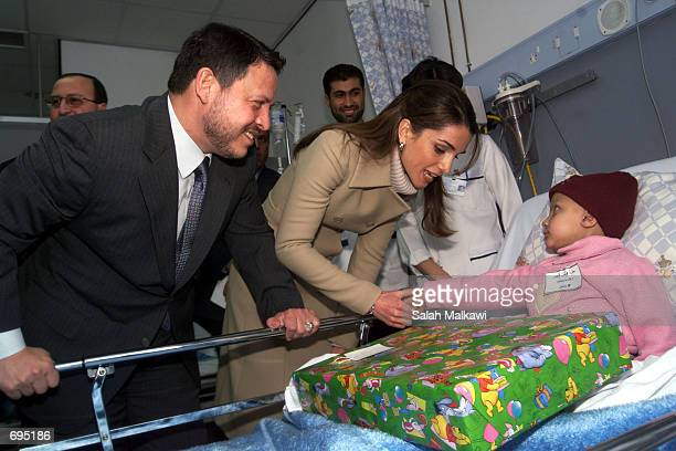 Queen Rania and Jordans King Abdullah give a present to a child being treated for cancer January 29 2002 at alAmal hospital in Amman Jordan King...