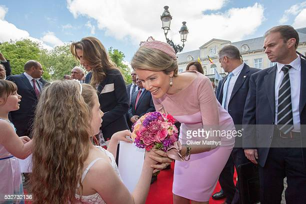 Queen Rania of Jordan and Queen Mathilde of Belgium receive a bouquet of flowers as they arrive at the Town Hall during a state visit by King...