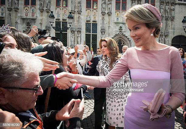 Queen Rania of Jordan and Queen Mathilde of Belgium shake hands with wellwishers during a royal guided tour through the city of Brugge as part of...