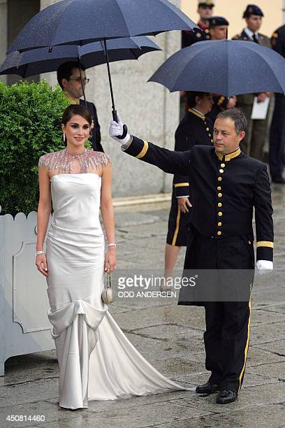 Queen Rania of Jordan poses for photographers as she arrives to attend an official diner at the Pardo Palace in Madrid 21 May 2004 on the eve of...