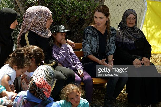 Queen Rania of Jordan speaks with migrants and refugees during her visit at the refugee site of Kara Tepe in Mytilene on April 25 2016 / AFP / ARIS...