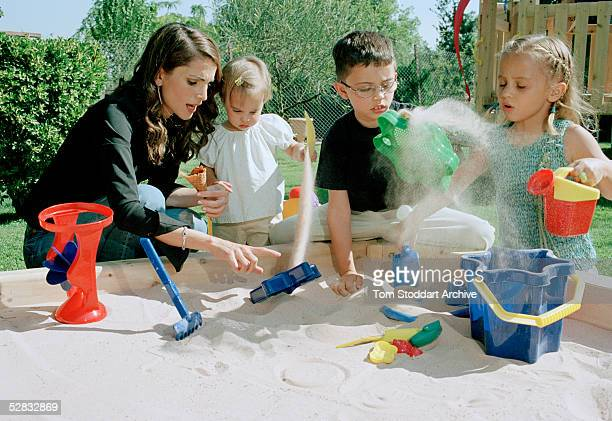 Queen Rania plays with her children Princess Salma, Prince Hussein and Princess Iman, in a sandpit at their home in Amman. Queen Rania Al-Abdullah...