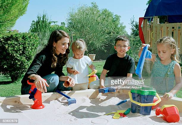 Queen Rania plays with her children Princess Salma Prince Hussein and Princess Iman in a sandpit at their home in Amman Queen Rania AlAbdullah was...