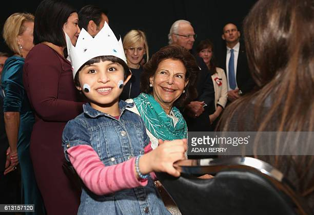 Queen Silvia of Sweden talks to sixyearold Syrian refugee Mnar during a visit to the Refugio refugee project part of the Give Something Back to...