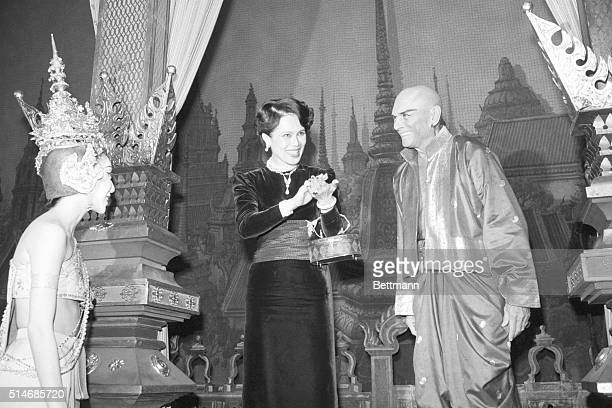 Queen Sirikit of Thailand applauds on stage after watching a performance of the King and I. Yul Brynner, who played the King of Siam, stands next...
