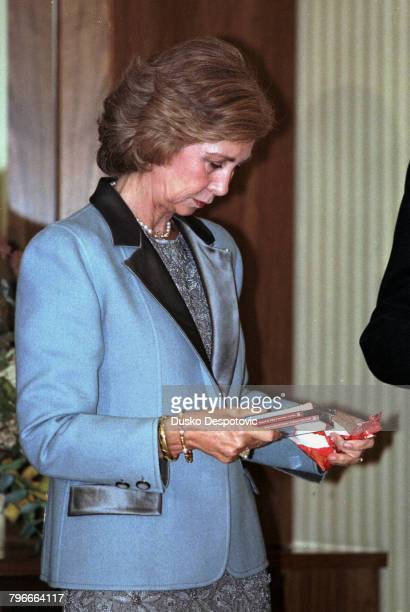 Queen Sofia looks at the CDs given to her by M Rostropovitch after the concert