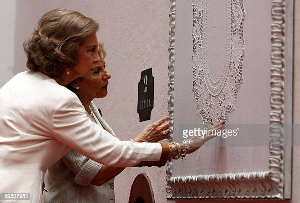 Queen Sofia of Spain and Portuguese first lady Maria Cavaco Silva look at a madeira embroidered artcraft in Funchal Madeira Island on July 31 on the...