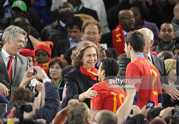Queen Sofia of Spain congratulates Spain's striker Pedro as Spain's defender Raul Albiol looks on during the award ceremony following their 2010 FIFA...