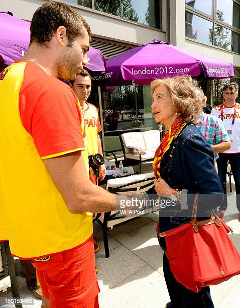 Queen Sofia of Spain is greeted by Spanish athlete Javier Garcia Gadea as she walks through the Olympic athletes village in Stratford east during a...