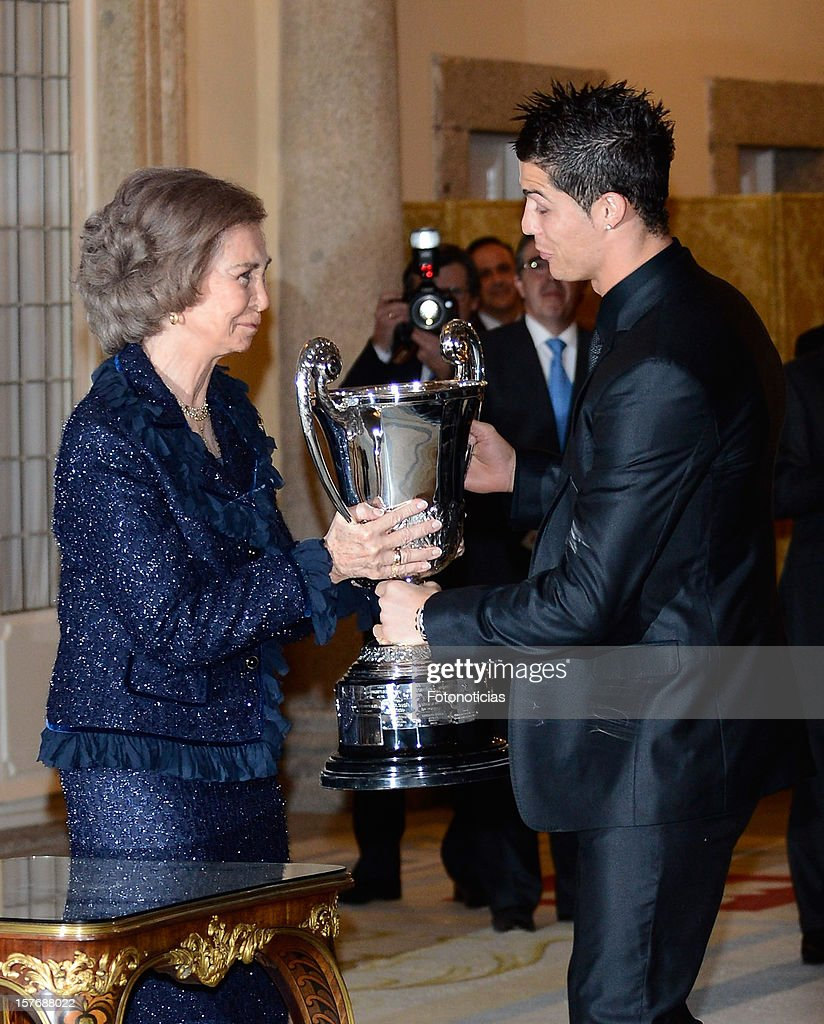 Queen Sofia of Spain (L) presents Real Madrid's Portuguese player Cristiano Ronaldo with the Ibero-American Community Trophy during the National Sports Awards ceremony at El Pardo Palace on December 5, 2012 in Madrid, Spain