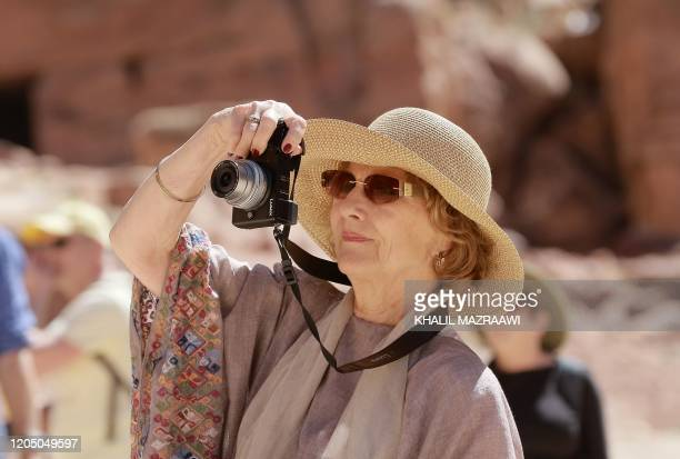 Queen Sonja of Norway takes photographs during a visit to Jordan's archaeological city of Petra south of the capital Amman on March 4 2020