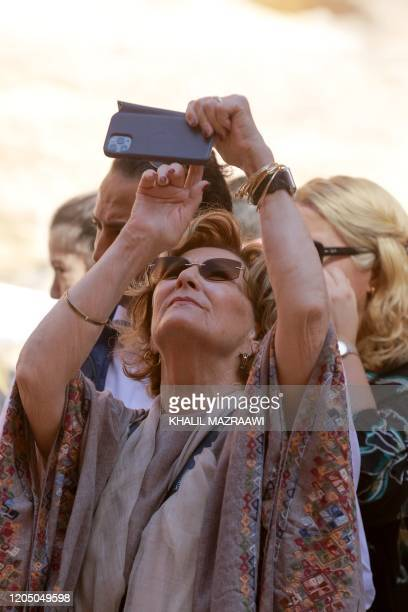 Queen Sonja of Norway takes photographs with her telephone during a visit to Jordan's archaeological city of Petra south of the capital Amman on...