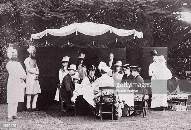 Queen Victoria holds a garden party with members of her family in the grounds of Osborne House on the Isle of Wight Two Indian servants wearing...