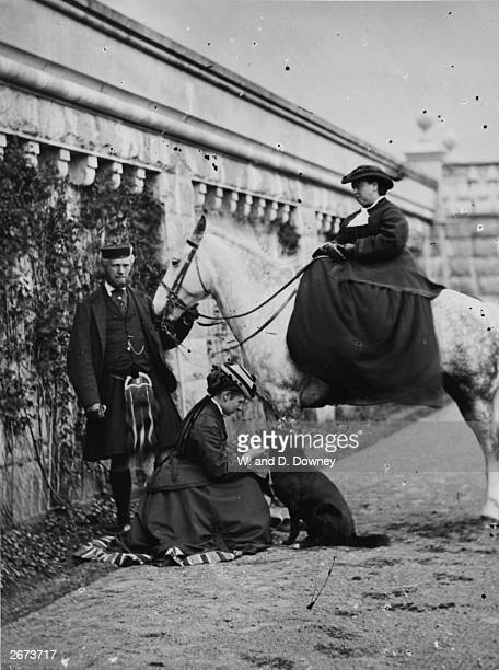 Queen Victoria mounted on a horse with her fourth daughter Princess Louise and her attendant John Brown at Balmoral Scotland Queen Victoria often...