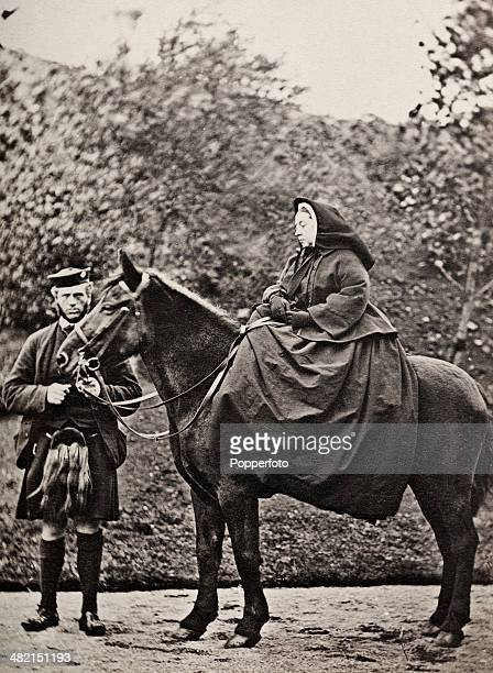 Queen Victoria on horseback with her ghillie John Brown at Balmoral Castle in Scotland circa 1863