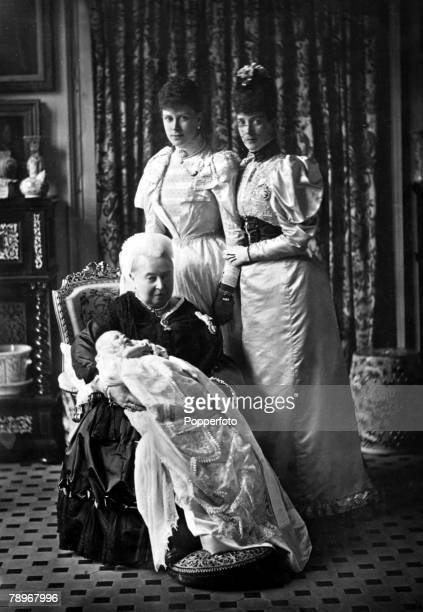 Queen Victoria sits with her grandson the baby Prince Edward on her knee on his christening while Alexandra and Mary stand behind them
