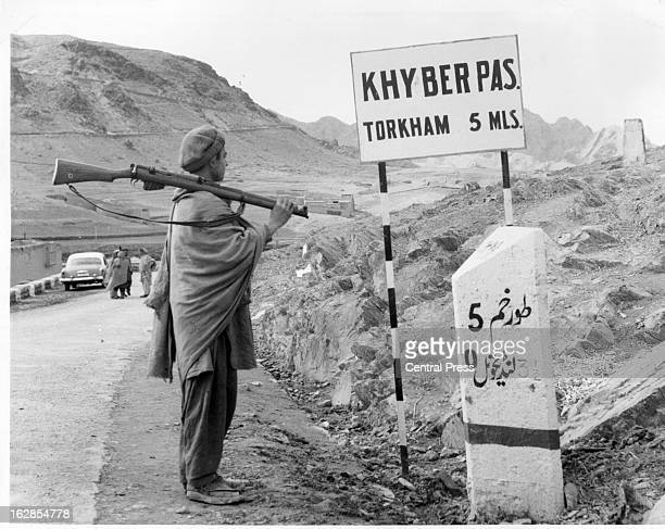 Queen visits Khyber Pass Cattleman armed with rifle standing at sign 7/2/1961