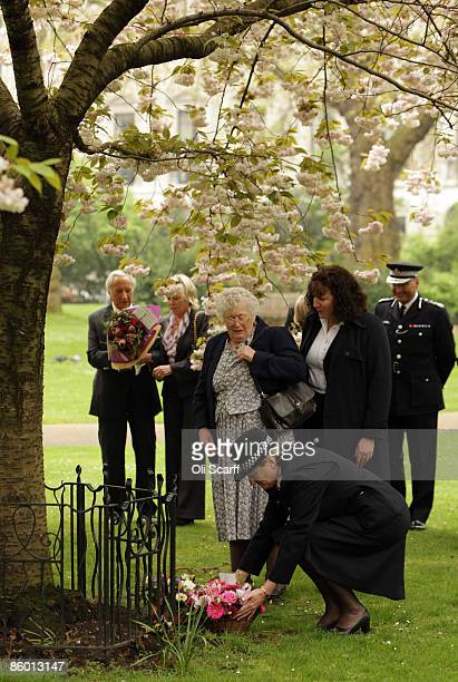 Queenie Fletcher the mother of Yvonne Fletcher watches as a police officer lays flowers by a tree planted in her daughter's honor at a ceremony to...