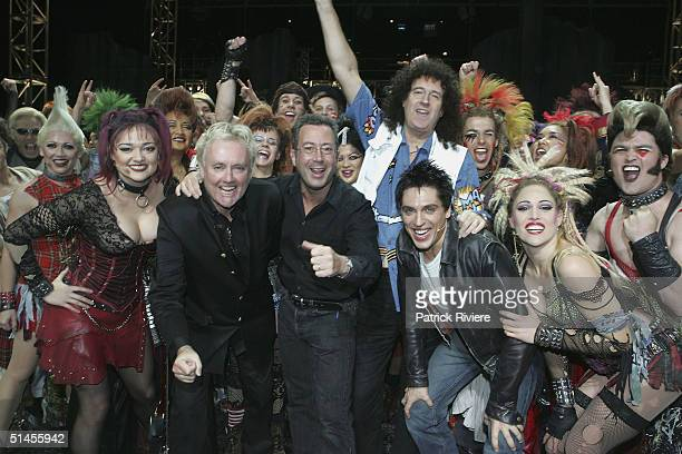 """Queen's founding members Roger Taylor and Brian May pose on stage with producer Ben Elton and the cast members of """"We Will Rock You"""" after a photo..."""